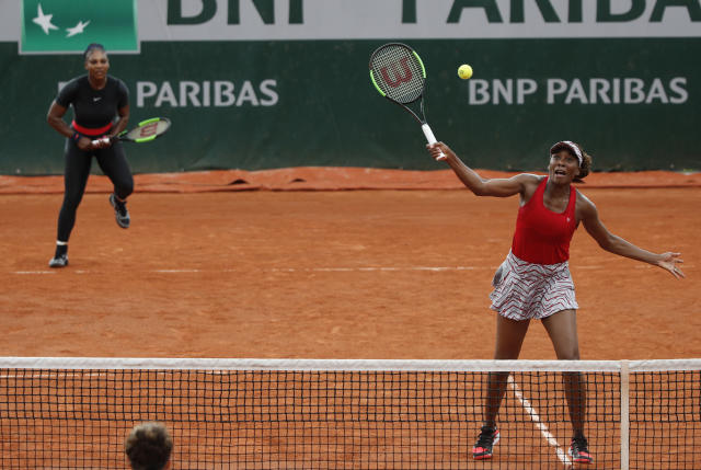 Venus Williams of the U.S., right, and her sister Serena Williams play Italy's Sara Errani and Belgium's Kirsten Flipkens during their doubles second round match of the French Open tennis tournament against at the Roland Garros stadium, Friday, June 1, 2018 in Paris. (AP Photo/Christophe Ena)