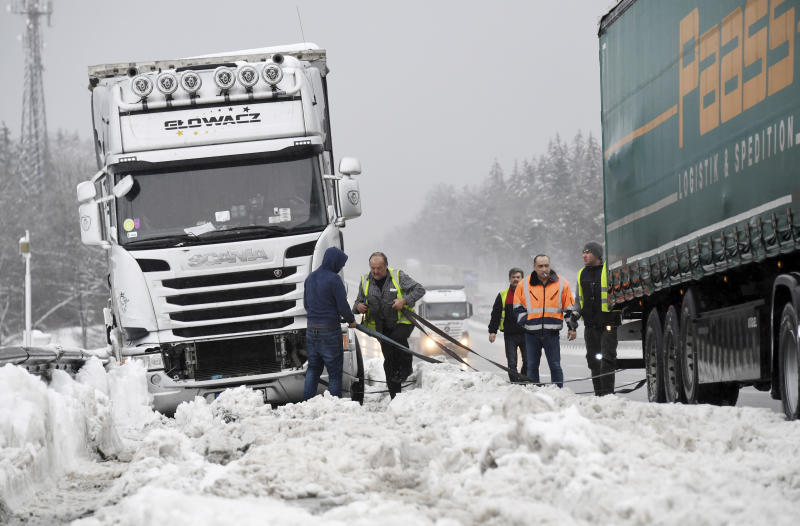 Truck drivers help each other after being trapped by heavy snowfall on the Autobahn A8 near Holzkirchen, southern Germany, Monday, Jan. 7, 2019. (Tobias Hase/dpa via AP)