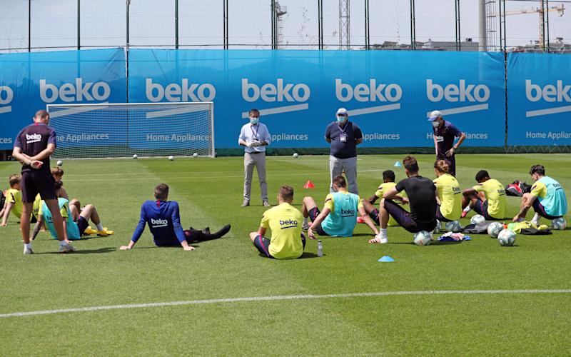 BARCELONA, SPAIN - MAY 23: President Josep Maria Bartomeu (C) of FC Barcelona talks to FC Barcelona players next to Head Coach Quique Setien (R) and CEO Oscar Grau (2nd R) during a training session at Ciutat Esportiva Joan Gamper on May 23, 2020 in Barcelona, Spain. Spanish LaLiga clubs are back training in groups of up to 10 players following the LaLiga's 'Return to Training' protocols. (Photo by Handout/FC Barcelona via Getty Images)