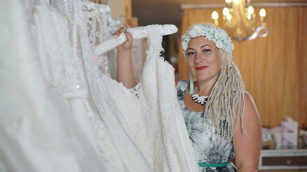 Samm Buca changed her name legally five years ago. She is seen here holding up a wedding dress.