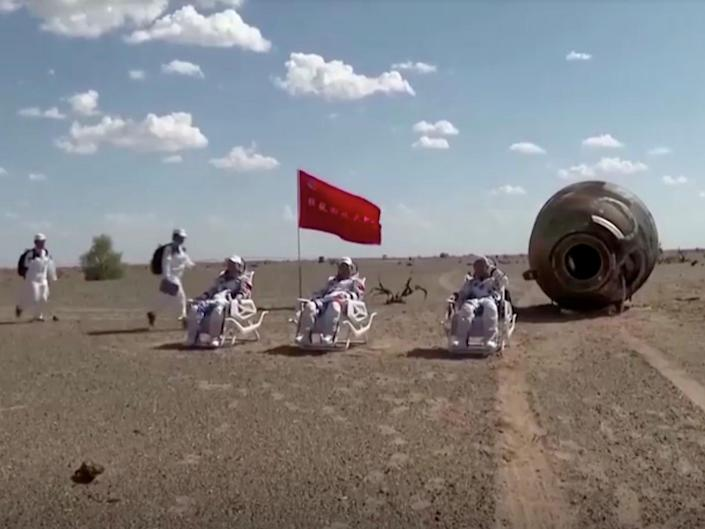 chinese astronauts sit in chairs next to charred spaceship after landing in mongolia desert from space station mission