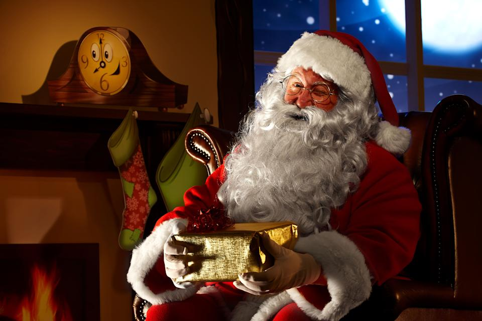 Close up of Santa holding a Christmas present (Photo: stocknroll via Getty Images)