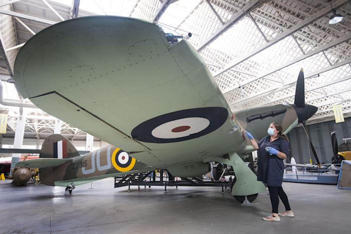 Embargoed to 0001 Tuesday September 15 File photo dated 18/08/20 of Samantha Archetti, Collections Care Technician, cleaning a Hurricane ahead of the reopening of the Battle of Britain exhibition at IWM Duxford, which marks 80 years since the German Luftwaffe began its air attacks at the start of the Battle of Britain. Issue date: Tuesday September 15, 2020. The battle was a major air campaign fought in the skies over the UK in 1940 and was the first battle in history fought entirely in the air. Though the battle took place between July and October 1940, September 15 saw the British Royal Air Force (RAF) gain a decisive victory over the Luftwaffe in what was Nazi Germany�s largest daylight attack. A variety of tributes and commemorations will take place across the UK to mark the 80th anniversary of the Battle of Britain despite limitations caused by the coronavirus crisis. See PA story MEMORIAL Battle. Photo credit should read: Victoria Jones/PA Wire