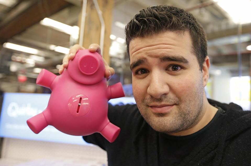 """In this Thursday, Nov. 21, 2013 photo, New York-based Quirky CEO Ben Kaufman holds a smart piggy bank his company markets at company headquarters, in New York. Kaufman created a staff """"blackout week"""" once each quarter in which no one besides the company's customer service representatives area allowed to work. The startup company shepherds inventions to the marketplace. (AP Photo/Kathy Willens)"""