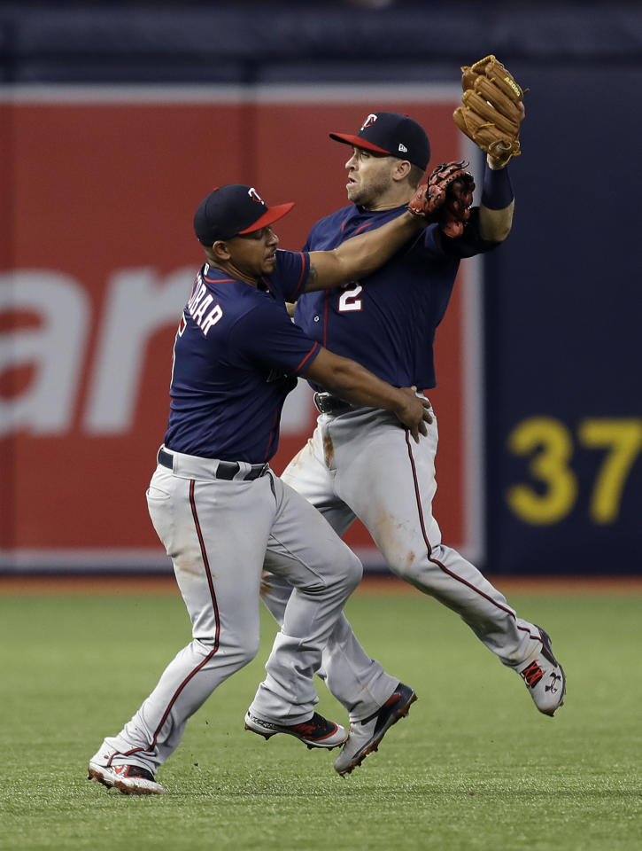 Minnesota Twins third baseman Eduardo Escobar, left, and second baseman Brian Dozier collide as Dozier was making the catch on a popup by Tampa Bay Rays' C.J. Cron during the third inning of a baseball game Friday, April 20, 2018, in St. Petersburg, Fla. (AP Photo/Chris O'Meara)