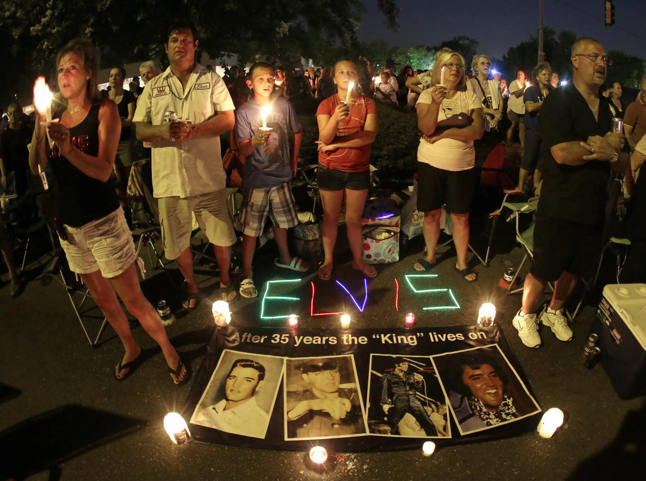 Elvis Presley fans take part in a candlelight vigil at Graceland, Presley's Memphis, Tenn. home, on Wednesday, Aug. 15, 2012. Fans from around the world are at Graceland to commemorate the 35th anniversary of Presley's death. (AP Photo/Mark Humphrey)