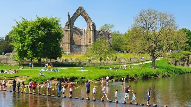 Venturing across the stepping stones at Bolton Abbey in North Yorkshire