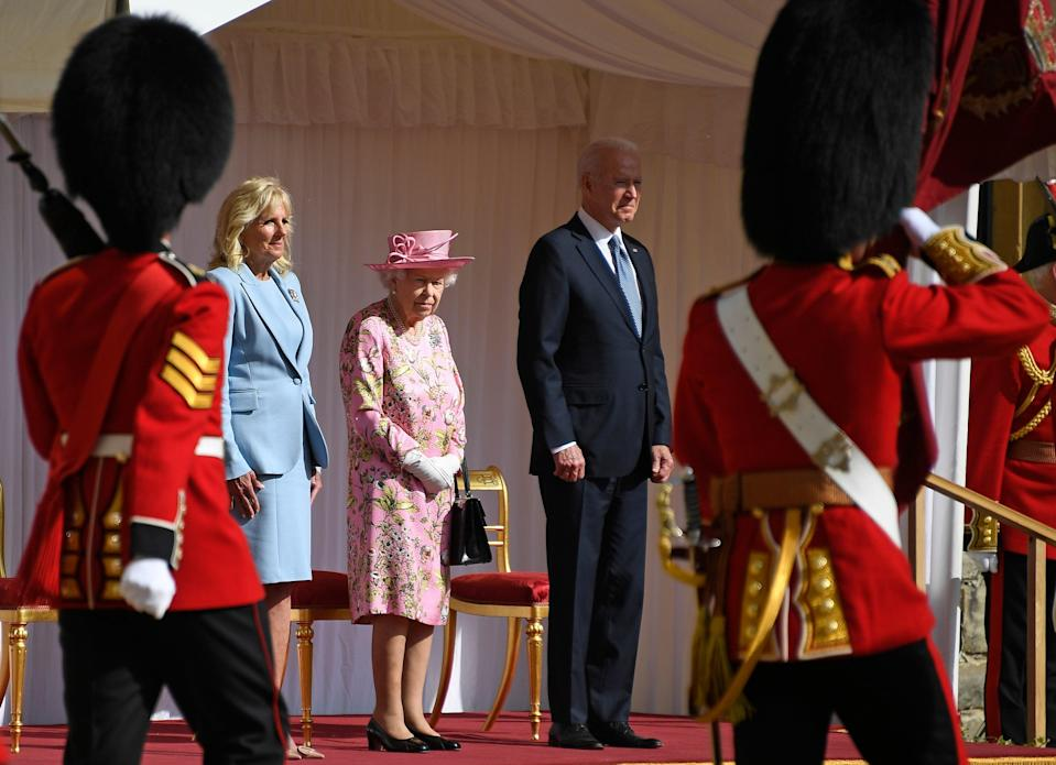 US President Joe Biden takes a salute from a Guard of Honour after arriving with First Lady Jill Biden to meet Britain's Queen (AP)