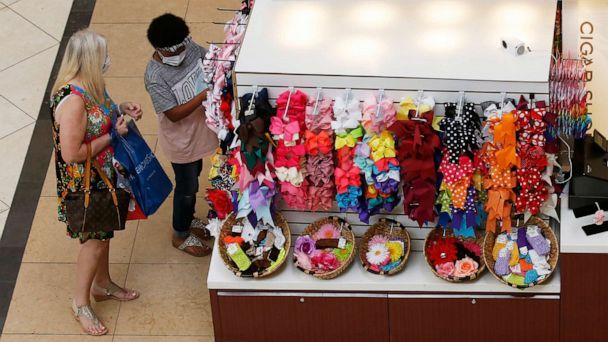 PHOTO: People shop at a kiosk at Penn Square Mall as the mall reopens, May 1, 2020, in Oklahoma City. (Sue Ogrocki/AP)