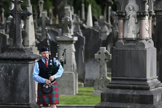A member of the Black Raven pipe band plays in Glasnevin cemetery