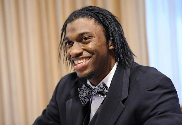 Washington Redskins quarterback Robert Griffin III, the team's Ed Block Courage Award winner, smiles during an autograph session at the Ed Block Courage Awards banquet in Baltimore Monday, March 17, 2014. The award, named for the late former trainer of the Baltimore Colts, recognizes a player from each team in the National Football League who has displayed courage in the face of adversity over the past year. (AP Photo/Steve Ruark)