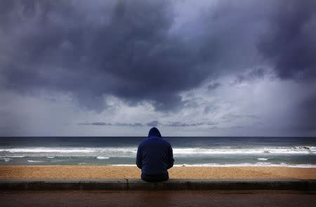 A surfer looks at waves as storm clouds move in from Pacific Ocean at Sydney's Manly Beach
