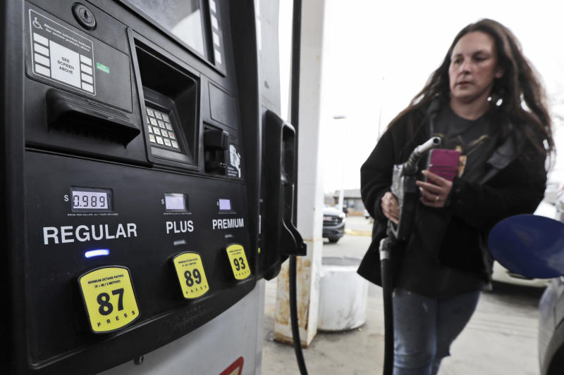 Heatherlee Madden puts the nozzle back after getting gas for 98.9 cents a gallon, Monday, March 30, 2020, in Cleveland. Oil started the year above $60 and has plunged on expectations that a weakened economy will burn less fuel. The world is awash in oil, meanwhile, as producers continue to pull more of it out of the ground. (AP Photo/Tony Dejak)