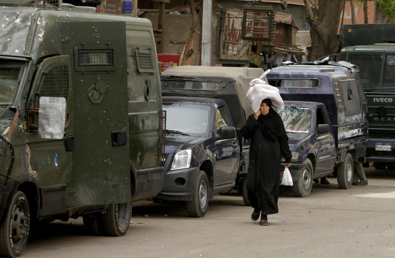 An Egyptian woman walks past anti-riot police vehicles near the Coptic cathedral in Cairo, Egypt, Monday, April 8, 2013. The death toll in clashes between Muslims and Christians in Cairo has risen to two, health and security officials said Monday. Another 89 were injured in the clashes outside Cairo's main Coptic cathedral, which brought Egypt's growing religious tension to the seat of the church's pope. (AP Photo/Amr Nabil)