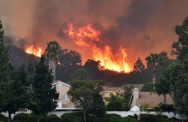<p>Flames from the Holy Fire shoot up above homes in Lake Elsinore, California, southeast of Los Angeles on Aug. 10, 2018. (Photo: Robyn Beck/AFP/Getty Images) </p>