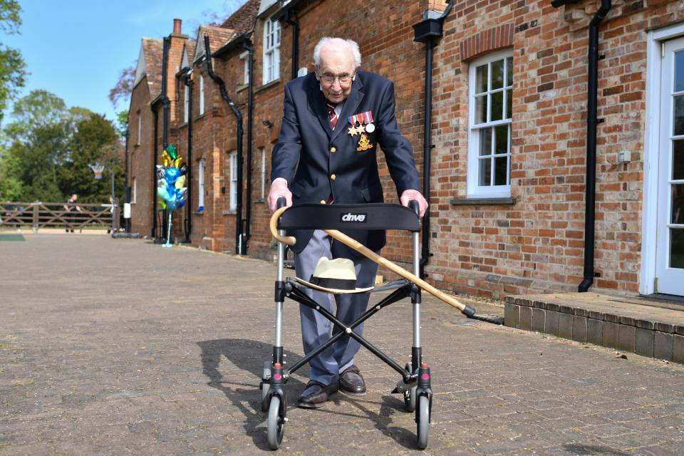 British World War II veteran Captain Tom Moore, 99, poses with his walking frame doing a lap of his garden in the village of Marston Moretaine, 50 miles north of London, on April 16, 2020. - A 99-year-old British World War II veteran Captain Tom Moore on April 16 completed 100 laps of his garden in a fundraising challenge for healthcare staff that has