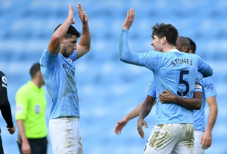 Ruben Dias (left) and John Stones struck to send Manchester City 13 points clear in the Premier League