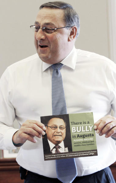 """In this Friday, April 27, 2012 photo, Gov. Paul LePage talks about his sense of humor while holding a poster that reads """"There is a bully in Augusta pushing around seniors, children and middle class families,"""" during an interview with the Associated Press at his office at the State House in Augusta, Maine. Critics are putting pressure on LePage to apologize for referring to the Internal Revenue Service as """"the new Gestapo"""" during his radio address Saturday, July 7, 2012. (AP Photo/Pat Wellenbach)"""