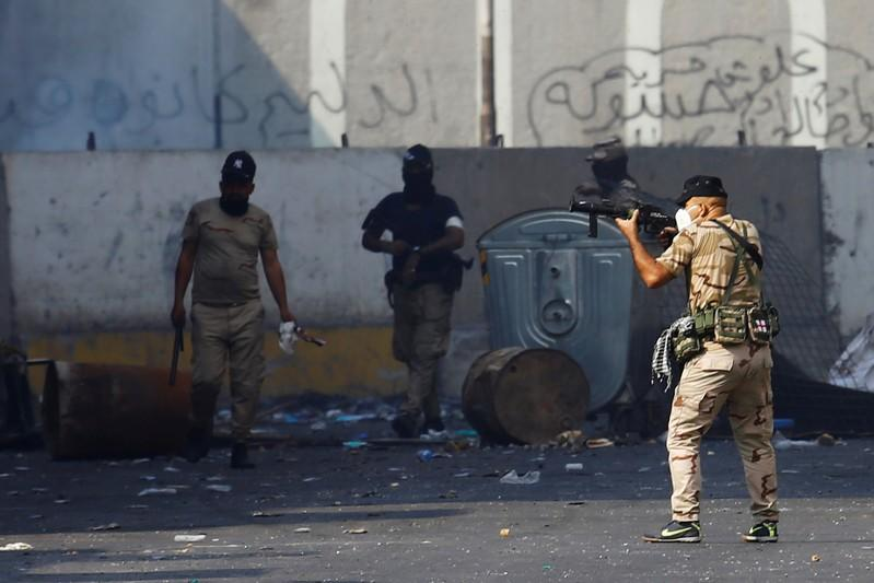 A member of Iraqi security forces points his gun towards the demonstrators during the ongoing anti-government protests in Baghdad