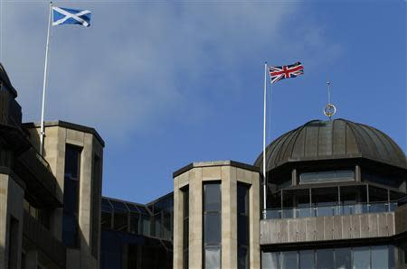 A Scottish Saltire flag (L) and a Union flag of the United Kingdom fly above Standard Life House in Edinburgh, Scotland February 27, 2014. Insurance and pensions heavyweight Standard Life became the first major company to warn it could move partly out of Scotland if Scots split from the United Kingdom, fuelling a political row over the financial impact of independence. REUTERS/Russell Cheyne