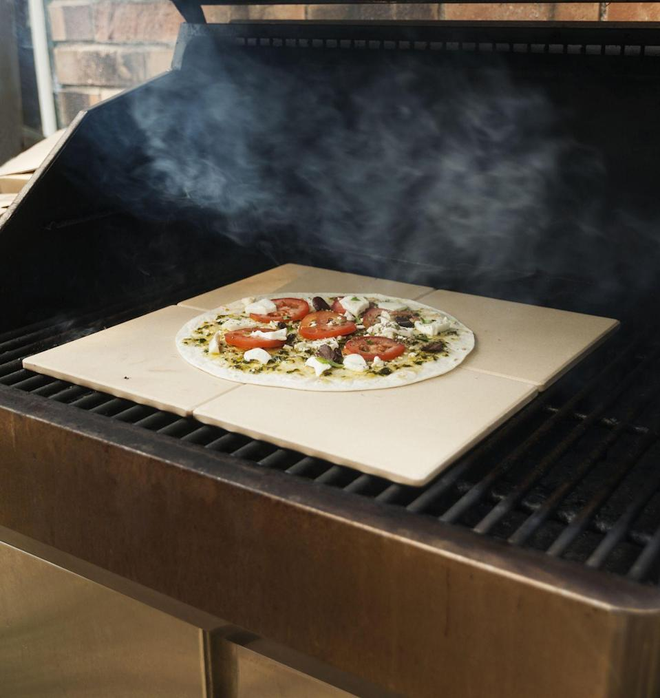 """<p>If you've never made homemade pizza on your grill before, it's definitely something you should try. But instead of just placing it on the grates, put it on a pizza stone to ensure uniform cooking. Also make sure you have some cornmeal handy. </p><p>""""With the pizza stone, you should also use cornmeal to slide the uncooked pizza on to the cornmeal-dusted pizza stone, to ensure that the pizza slides right off the stone without sticking when the pizza is done cooking,"""" Randhawa says. """"The cornmeal also adds great flavor to the crust without any oils or sprays."""" </p>"""