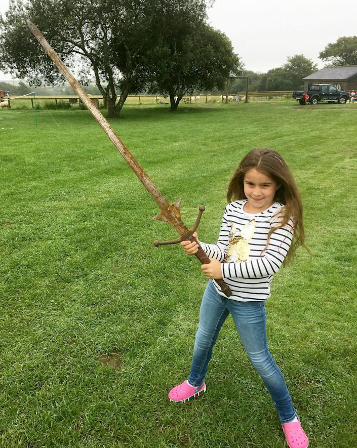 Matilda Jones, from Norton, Doncaster, shows off a mighty sword that she found at the bottom of a lake where King Arthur's said to have returned his Excalibur. (Photo: SWNS)