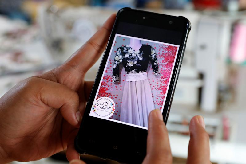 Asnia Muloc Sandiman, 25, shows a photo of a dress she made using a sewing machine provided by the government, in her family's tent at an evacuation camp in Marawi City, Lanao del Sur province, Philippines. (Photo: Eloisa Lopez/Reuters)
