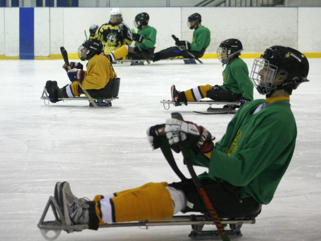 Young members of the Hornets youth sled hockey team prepare to play during a team practice in Addison, Ill. on Tuesday, Feb. 11, 2014. Brody Roybal, a high school sophomore, played on the team until he was 12. Now 15, he is the youngest member of the U.S. Paralympic sled hockey team which will play in Sochi, Russia in March 2014. Sled hockey allows people who can't use traditional skates to play the game. (AP Photo/Martha Irvine)
