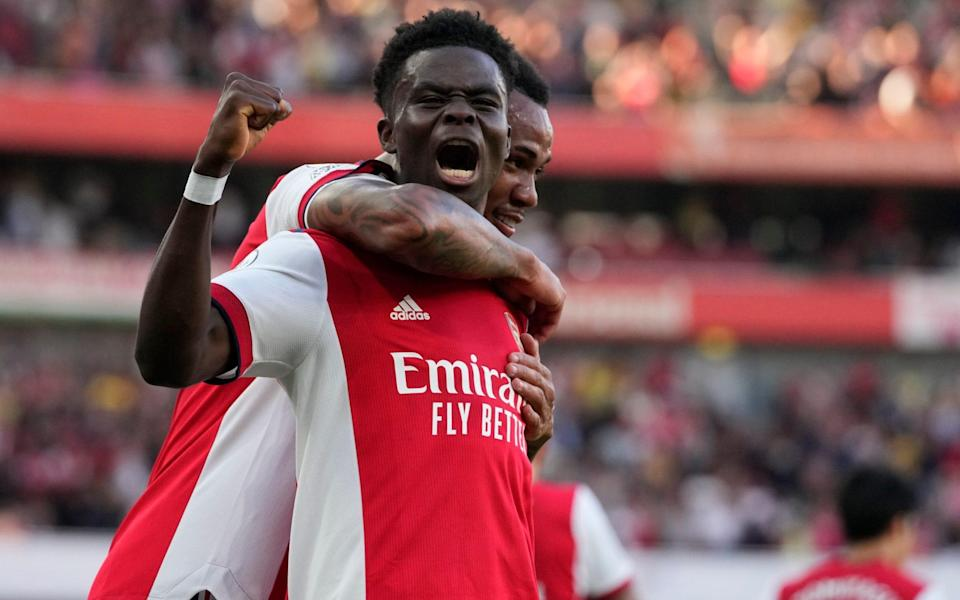 Arsenal's Bukayo Saka, front, celebrates after scoring his side's third goal during the English Premier League soccer match between Arsenal and Tottenham Hotspur at the Emirates stadium in London, Sunday, Sept. 26, 2021. - AP