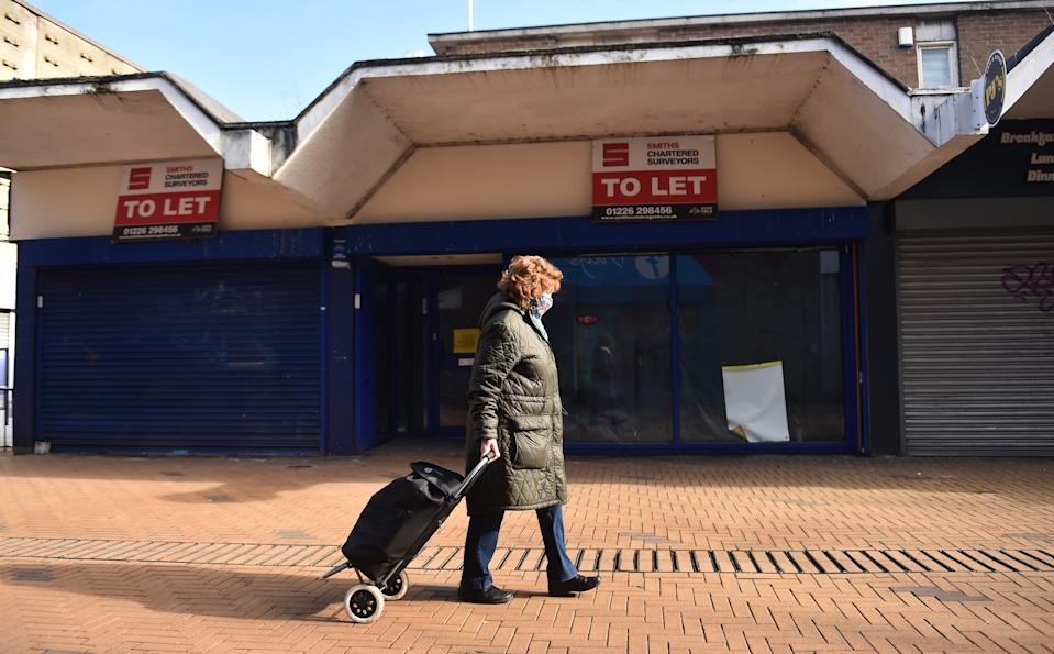 BARNSLEY-ENGLAND - FEBRUARY 27: A lady walks past a closed shop which is To Let on February 27, 2021 in Barnsley, England . (Photo by Nathan Stirk/Getty Images) (Photo by Nathan Stirk/Getty Images)