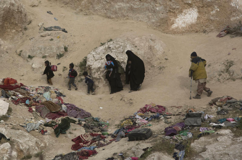 Women, children, and an injured man who left the besieged Islamic State-held village of Baghouz, Syria, scramble over a rocky hillside to be checked by U.S-backed Syrian Democratic Forces, Thursday, March 14, 2019. (AP Photo/Maya Alleruzzo)
