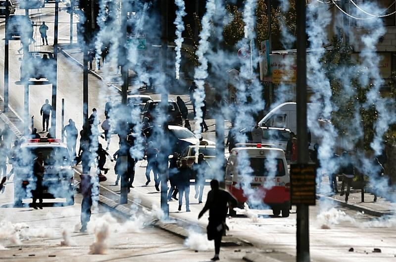 Palestinian stone throwers run to take cover after Israeli security forces fire tear gas canisters during clashes in the West Bank city of Bethlehem, on December 18, 2015 (AFP Photo/Thomas Coex)