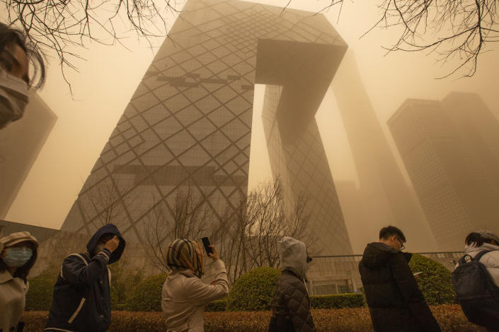 Employees line up at a security checkpoint outside the China Central Television (CCTV) building amid a sandstorm during the morning rush hour in Beijing, Monday, March 15, 2021. The sandstorm brought a tinted haze to Beijing's skies and sent air quality indices soaring on Monday. (AP Photo/Mark Schiefelbein)