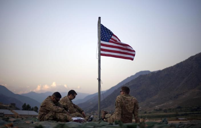 FILE - In this Sept. 11, 2011 file photo, US soldiers sit beneath an American flag just raised to commemorate the tenth anniversary of the 9/11 attacks at Forward Operating Base Bostick in Kunar province, Afghanistan. The Biden administration's surprise announcement in April 2021, of an unconditional troop withdrawal from Afghanistan by Sept. 11, 2021, appears to strip the Taliban and the Afghan government of considerable leverage, pressuring them to reach a peace deal. (AP Photo/David Goldman, File)