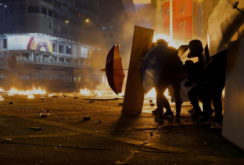Protestors react as police fire tear gas in the Kowloon area of Hong Kong, Monday, Nov. 18, 2019. As night fell in Hong Kong, police tightened a siege Monday at a university campus as hundreds of anti-government protesters trapped inside sought to escape. (AP Photo/Vincent Yu)