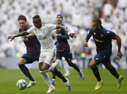 Real Madrid's Vinicius Junior, second left, vies for the ball during the Spanish La Liga soccer match between Real Madrid and Levante at the Santiago Bernabeu stadium in Madrid, Spain, Saturday, Sept. 14, 2019. (AP Photo/Bernat Armangue)