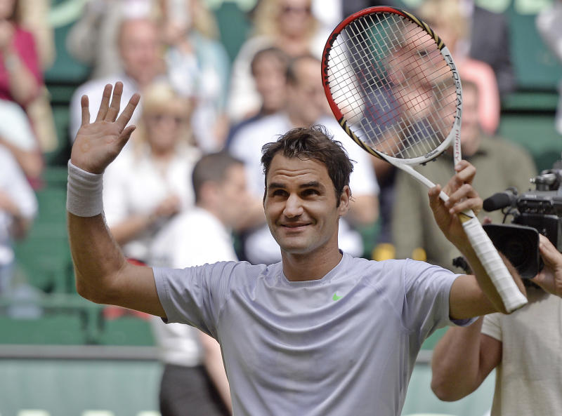 Switzerland's Roger Federer celebrates after winning the final against Mikhail Youzhny of Russia at the Gerry Weber Open tennis tournament in Halle Westphalia, Germany, Sunday, June 16, 2013. Roger Federer won his first title of the year, overcoming a sluggish start to beat unseeded Mikhail Youzhny 6-7 (5), 6-3, 6-4 at the Gerry Weber Open on Sunday. Returning to grass in his favorite warm-up for Wimbledon, the top-seeded Federer looked lethargic until the middle of the second set, when he started hitting shots with confidence. Federer won his first title since Cincinnati in August and his sixth in Halle, the first since 2008. (AP Photo/Martin Meissner)