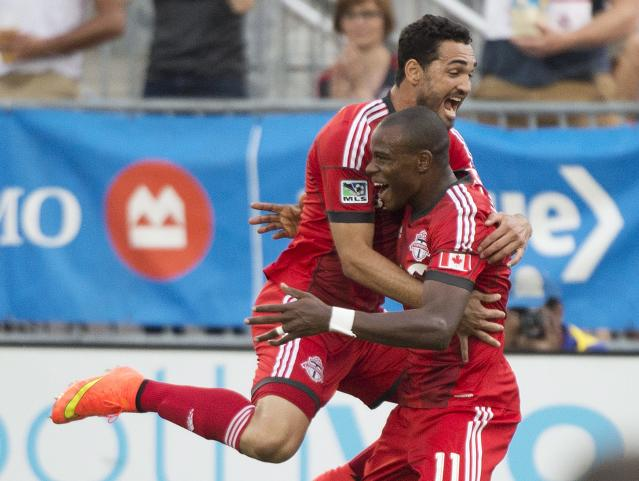 Toronto FC midfielder Jackson, right, celebrates with teammate Gilberto, left, after scoring against Sporting Kansas City during the first half of an MLS soccer game Saturday, July 26, 2014, in Toronto. (AP Photo/The Canadian Press, Nathan Denette)