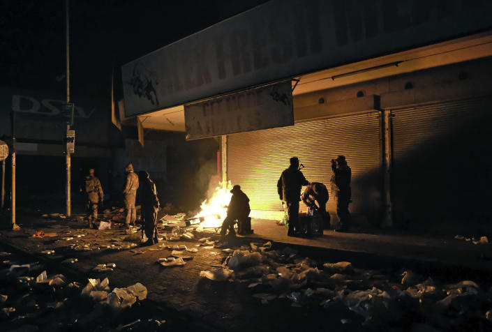 South African Defence Force soldiers keep themselves warm around a fire while stationed in Alexandra Township, near Johannesburg, to assist police in quelling looting and rioting Tuesday, July 13, 2021. South Africa's police say 72 people have been killed and 1,234 have been arrested in unrest set off by the imprisonment last week of former President Jacob Zuma. (AP Photo/Dino Lloyd)