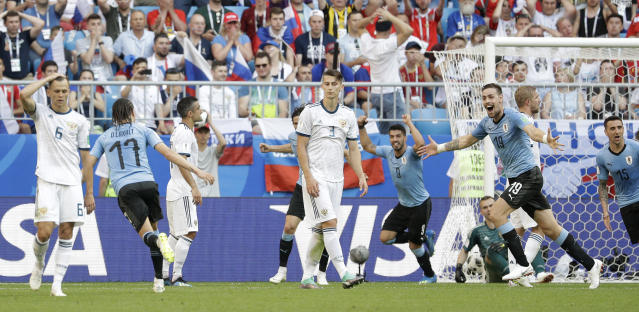 Uruguay's Diego Laxalt, second left, scores his side's second goal during the group A match between Uruguay and Russia at the 2018 soccer World Cup at the Samara Arena in Samara, Russia, Monday, June 25, 2018. (AP Photo/Gregorio Borgia)