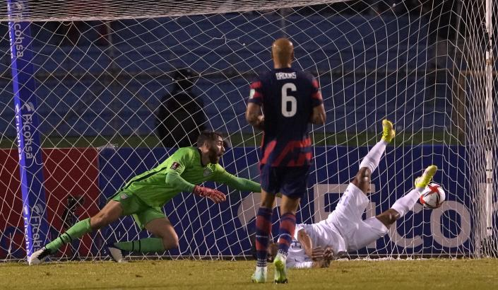 CORRECTS GOAL SCORER - Goalkeeper Matt Turner of the United States, left, tries to stop a shot on goal by Hondura's Brayan Velasquez, scoring his side's opening goal against the United States during a qualifying soccer match for the FIFA World Cup Qatar 2022, in San Pedro Sula, Honduras, Wednesday, Sept. 8, 2021. (AP Photo/Moises Castillo)