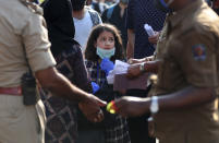 A stranded Kashmiri girl anxiously looks at officials checking documents as she waits with elders to board a bus to a special train home during a lockdown to curb the spread of new coronavirus, in Bangalore, India, Sunday, May 10, 2020. India's lockdown entered a sixth week on Sunday, though some restrictions have been eased for self-employed people unable to access government support to return to work. (Aijaz Rahi)