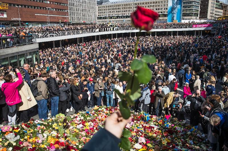 People attend a memorial ceremony on April 9, 2017 at Sergels Torg plaza in Stockholm, close to the point where a truck drove into a department store two days before