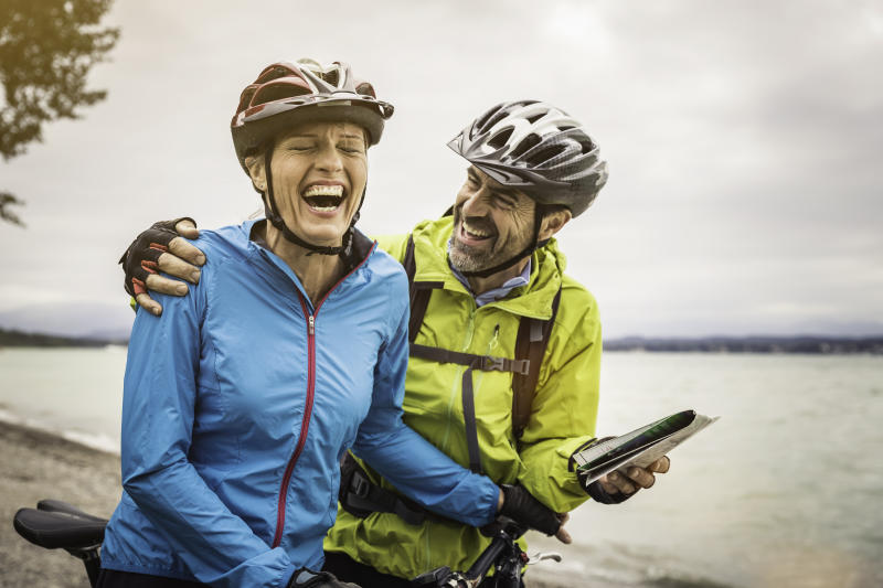Mature mountain biking couple laughing whilst checking map at lakeside