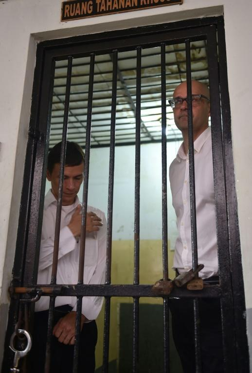 Indonesian teaching assistant Ferdinand Tjiong (L) and Canadian school administrator Neil Bantleman (R) waiting inside a court detention cell in Jakarta