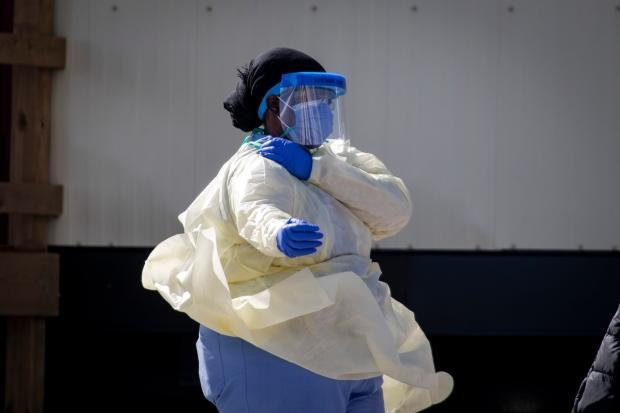 A staff member at an Ontario long-term care home is pictured wearing full personal protective equipment amid an outbreak among the residents. (Evan Mitsui/CBC - image credit)