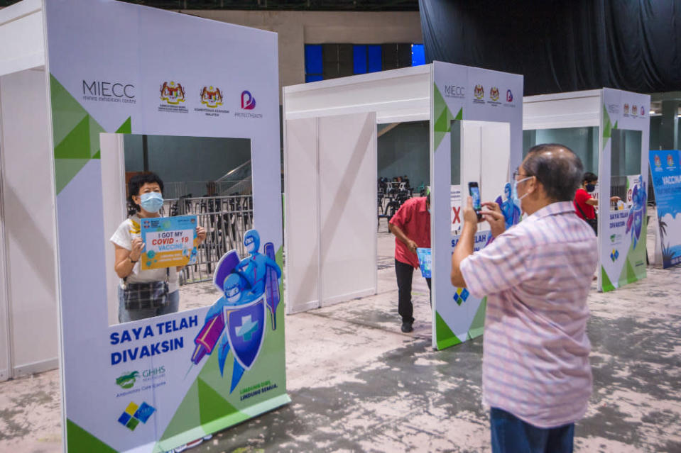 People pose for pictures after their jabs at the Covid-19 vaccination centre in the Mines International Exhibition and Convention Centre, Seri Kembangan, June 17, 2021. — Picture by Shafwan Zaidon