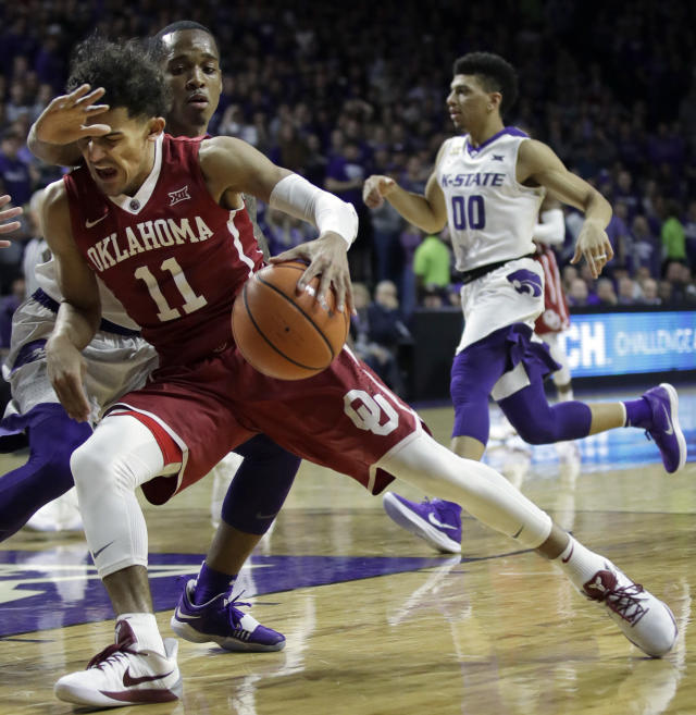 Oklahoma guard Trae Young (11) is fouled by Kansas State guard Barry Brown, back, during the first half of an NCAA college basketball game in Manhattan, Kan., Tuesday, Jan. 16, 2018. (AP Photo/Orlin Wagner)