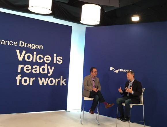 Two people in chairs in front of Nuance logo with slogan regarding Dragon on opposite blue wall.