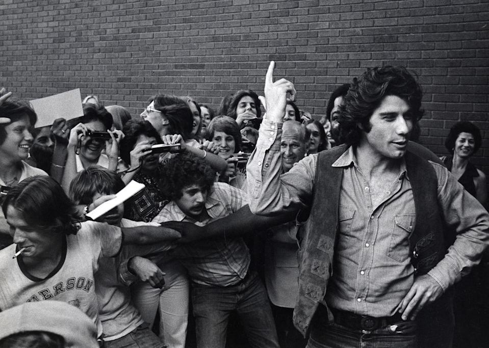 <p>Travolta was photographed with adoring fans backstage on Broadway, after opening in <em>Bus Stop</em> in 1976.</p>